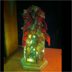 This is a Christmas lantern I made by drilling a hole in the bottom, to feed white Christmas lights through. I also used cinnamon scented pine cones, which I sprayed with craft adhesive and sprinkled with clear/white glitter to reflect the lights.  The warmth from the lights really enhanced the fragrance!  And finally, topped it with a bow made from both plaid and pine cone printed wire ribbon.  Merry Christmas!