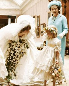 July 29, 1981 Princess Diana comforts her youngest bridesmaids, Clementine Hambro, age five, behind the scenes at Buckingham Palace in London after the wedding ceremony. Also seen in this photograph, captured by the royal photographer Lord Lichfield, H.M. The Queen