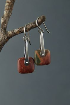 Two rounded-square stones in Red Creek Jasper, are pinned in place in a sterling silver stirrup shape. They swivel freely in place. The metal has a