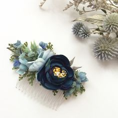 This navy flower comb is created with a stunning combination of navy ranunculus, blue cherry blossoms, ferns and berry accents tucked amongst the greenery. The piece is placed on a comb. Custom colors are available.  Size: 4.5 inches long  This is a one of a kind headpiece hand crafted with the finest materials in our Nova Scotian studio. Oh Dina! millinery has been featured in Style Me Pretty, Weddingbells Magazine, Flare Magazine, and the National Post, just to name a few! This headpiece…