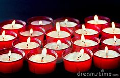 Group of red lighted votive candles or night lights with black background.