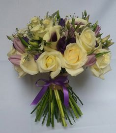 Hand tied bridal bouquet using purple lisianthus cream avalanche roses lilac tulips and vermeer callas....