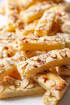 almond cookies a plate of almond butter stick cookies topped with sliced almonds Köstliche Desserts, Delicious Desserts, Dessert Recipes, Yummy Food, Puff Pastry Desserts, Dessert Tray, Almond Recipes, Baking Recipes, Almond Butter Cookies