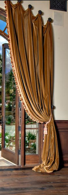 Velvet draperies draped from European Medallions echoing the line of the arched window. Luxury Draperies in Old World styles are available through DesignNashville.com, in business for 25 years, serving world wide since 2007