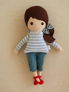 This is a handmade cloth doll measuring 18 inches. She is wearing a long sleeved gray and white striped knit shirt, cropped denim pants, and bright red maryjanes. Her long dark brown hair is worn in a side ponytail and accented with a white and black houndstooth check bow. She is made from 100% cotton fabrics, repurposed cotton knit and denim, wool felt, and polyester fiberfill. Her seams have been triple stitched, and she is firmly stuffed with fiberfill.    Please handwash only.    Thank…