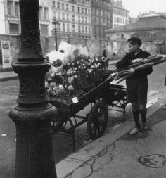 Robert Doisneau - Voiture de Quatre-Saisons: Les Fleurs de la Place du Marche Saint-Honore [Le Grosse aux Baguettes] 1946