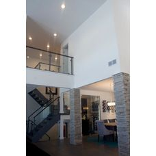 Modern Contemporary Home. Vaulted ceiling, glass wall staircase, gray wood floor, open dining room, glass wall wet bar, wine room, stone columns. recessed lights.
