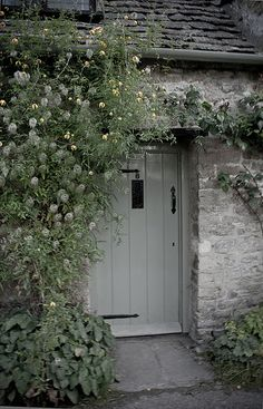Soft shades of gray repeated in the cottage colors and ... the flowers clamoring up the doorway.