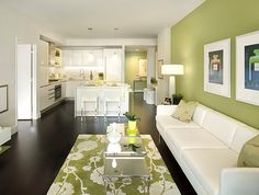 """Lighter green walls make for a sleek, modern look. White contrasting notes keep the room crisp, bright, and """"big""""; dark wood floors prevent it all from seeming """"novel"""". Try warmer up/down lighting near/on the wall. White baseboards and ceiling trim could make this less bold."""