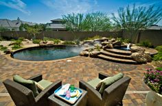 Natural #pool with raised #spa and rock waterfall surrounded by patterned #pavers. http://calpool.com