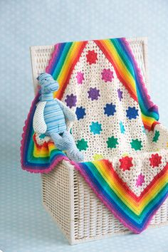 Rainbow Droplets Babyghan - This sweet little blanket was created to welcome in the sunshine. It is made of a rainbow of flowers with a rainbow border. This blanket is sure to brighten up any nursery. From the August 2015 issue of I Like Crochet