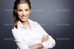 Portrét krásné mladé obchodní ženy stojící proti šedé pozadí