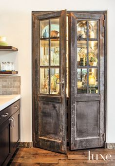Simon Pearce glassware, Vietri dishes and antique Talavera pottery fill a hutch in the kitchen. An existing element complete with antique French doors, Anderson had it lit from within to better function for display.