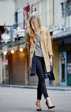 Outfit: Damsel in Dior wears a camel coat, stripe tee, black skinny jeans, and black pointed-toe pumps, via @sarahsarna.