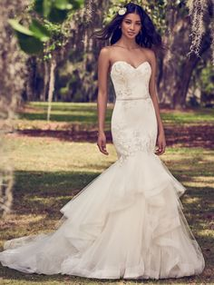 Mermaid wedding dress Dalinda features a tulle bodice accented in embroidered lace motifs atop a tiered tulle fit-and-flare skirt edged in horsehair. Lined with shapewear for a figure-flattering fit.