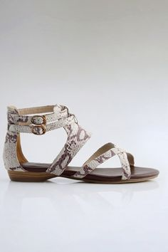 Sandals crafted in leather, featuring snake effect to the main, cross over foot strap to front, twin ankle straps with pin buckle closure, with a flat rubber sole.