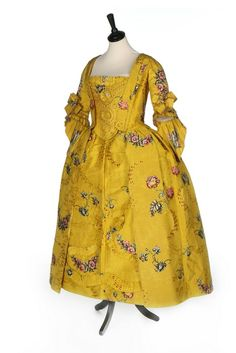 Robe à l'anglaise, England (Spitalfields), c. 1750. Yellow brocaded silk, woven with brightly coloured large-scale oriental poppies, posies and swags, the ground figured with arabesques and wine silk spotted cartouches, linen lining, trimmed with pinked furbelows; stomacher trimmed with rosettes and braid.