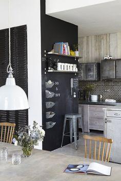 un mur ardoise pense-bête + les livres de cuisine en étagère au dessus de la porte