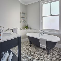 Monochrome-bathroom-with-patterned-tiles-and-roll-top-bath-2