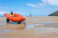 An orange rigid inflatable boat resting on a trailer on a Cornish. Rigid Inflatable Boat, Surfboard, Stock Photos, Beach, Photography, Image, Poster, Products, Photograph
