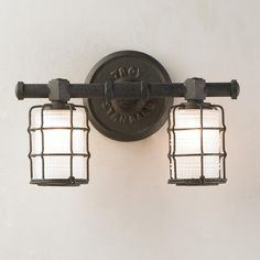 Vintage Bronze Caged Sconce - 2 Light A vintage replicated bath sconce with a caged light in vintage bronze takes your bathroom to a different period. Hand worked wrought iron and frosted pressed glass look perfect on either side of a mirror or use one of the lights from this collection above your mirror to add light and inspire a vintage theme. One, two, three and four light versions available.