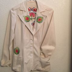 Authentic Vintage handmade white blazer This white blazer was created in the mid 70's. Handmade completely down to the intricate colorful stitching on front and circle design on back. The back is gathered at the waist. The front has fabric covered buttons with 2 front pockets. The cuffs are adjustable with a button strap. Worn once. Dry cleaned and kept in storage. The unique design and use of color makes this truly a one of a kind. It is a original designed and created by professional…