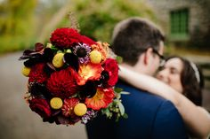 Bride and groom with fall-inspired flower bouquet - yellow belly buttons, red roses and dahlias with orange and purple accents. Willowdale Estate, a weddings and events venue in New England. WillowdaleEstate.com | Dan Aguirre Photography