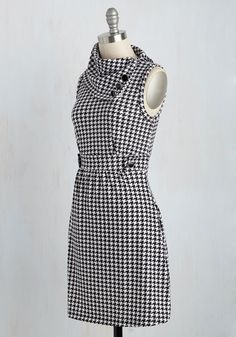 Sometimes a dress is so magical, it makes you long for somewhere special and new to wear it. Perfect for an old-style ride through sunny San Francisco, this black and white, houndstooth-printed dress features a carefully falling cowl neck, adorned by three black buttons, and a form-fitting waistband embellished by the same clasps. As you ride through this city and others, dolled up with a big bangle, sweet headscarf, and soft flats, this comfortable sleeveless dress lets you curl up in your…