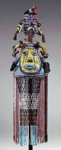 Africa   Royal crown from the Yoruba people of Nigeria   ca. 1920   Glass beads, leather, canvas, wicker   Among the Yoruba the use of beaded accessories was restricted to kings, priests and priestesses, and herbalist-diviners. Only kings however could enjoy the full range of beaded regalia such as slippers, fans, fly whisks, footrests, canes, staffs, thrones and crowns. Among the most important elements of an Oba's official ceremonial dress are tall, conical beaded crowns (adénlá).