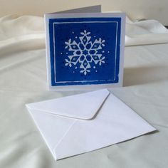 A  lino printed Christmas card - blue snowflake with glitter finish