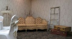Victorian Couch in a butterscotch color with large window frame, suitcases and a fringed up cycled floor lamp.| Vintage Events & Rentals.