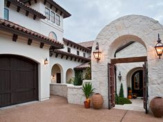 This luxurious home features a landscaped courtyard with arched stone gate and an infinity pool out back. Spanish style ceiling beams and arched doorways can be found throughout the interior in the kitchen, dining room, hallways, living room, and bedrooms.