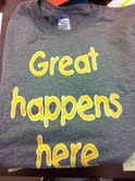 """Leader in Me T-SHIRTS similar to the W. T. Brown staff shirts.  They state """"Great Happens Here"""" on the front and """"You are following a leader from W. T. Brown Elementary School of Leadership"""" on the back.  They are gray with yellow lettering."""