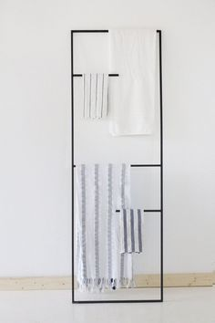 13 Ideas For Creating A More Manly, Masculine Bathroom // If wall hooks aren't your thing, you could use a metal leaning ladder instead, to display your towels and help them dry faster. The dark metal of this one helps to create a more minimalist masculine feel.