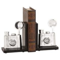 "Add antique-inspired appeal to your home library or living room with this industrial-chic bookend, showcasing a camera silhouette and black and silver finish.  Product: Set of 2 bookendsConstruction Material: Aluminum and engineered woodColor: Black and silverDimensions: 7"" H x 6"" W x 4"" D"