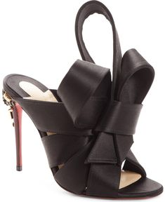 A spectacular bow detail at the vamp is beautifully matched by a studded stiletto heel on a peep-toe mule that brings the drama