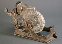 """Tatum – Snail, Revolving Inkwell with Penrest  An American made revolving 'snail' inkwell with a clear ribbed font by Tatum.  Maker: Tatum (unsigned), impressed """"1878″ Date: c. 1880  Price:$340 USD"""
