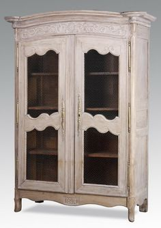 """19th century French Provincial style paint decorated carved oak armoire, the curved rectangular top surmounting a conforming case with two doors, the cartouches composed of wire mesh, opening to reveal four shelves, with """"1827"""" carved on the apron, raised on spade and bracket feet. 102""""h x 53""""w x 23""""d."""
