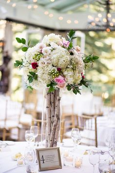 Wedding a the Sonnenalp Resort in Vail, Colorado.  Tall cylinder vases with aspen branches and a lush floral arrangement on top designed with white hydrangeas, pink roses, queen annes lace, and white roses. Photography by Jamee Photography. Florals by www.vailvintagemagnolia.com