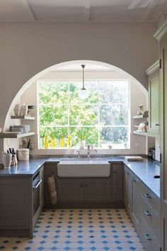 Arched window and grey cabinets in a modern schoolhouse kitchen