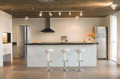 """Na cozinha de lazer deste refúgio em Xangri-Lá, RS, o teto de concreto aparente contrasta com as luminárias brancas (Interlight, compradas na Comercial Elétrica São Pedro). """"Presa direto na laje, a régua com cinco spots pontua o balcão. Lâmpadas PAR 20 deixam a iluminação mais quente e agradável"""", justifica o arquiteto Cristiano Lindenmeyer Kunze, sócio de Nathalia Cantergiani, da Cantergiani+Kunze Arquitetos. As demais luminárias, com o mesmo tipo de efeito, servem de luz geral."""
