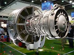 An exposed jet engine at a trade show. The rear of the polished metal fan Turbine Engine, Gas Turbine, Aeroplane Engine, Turbofan Engine, Aircraft Engine, Combustion Chamber, Flying Boat, Jet Engine, Mechanical Engineering