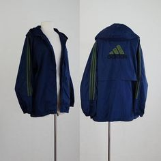 Vintage Adidas jacket. Navy blue nylon fabric with Adidas logo on the back. Dark green trim and embroidery. Zip-off hood. Jacket zips up the front. Jacket is labeled adult size medium, runs a little big.  M 46 chest 44 waist 27 length  Good vintage condition. There are some