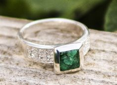Indulge in sheer sublimity with this luxurious Emerald ring. 1.25 carats of genuine Colombian Emerald gemstone fragments inlaid in resin and cradled in a stunning 925 sterling silver cubic frame accented by 12 cubic zirconia harmoniously matching its unique design.