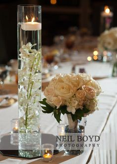 White flowers in water for floating candle vases at wedding reception for table centerpiece.