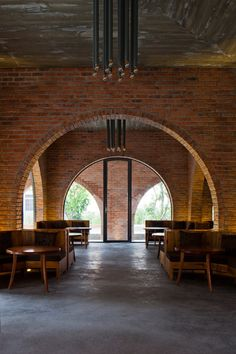 A grid of 24 red brick arches frames the interior of this Vietnam coffee shop.