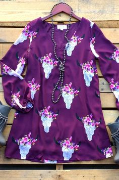 Our Western Nights Dress is a must have! It's a long sleeve tunic dress with bullhead print and flowers. V-neckline and made to be loose fitted. Is lined for extra coverage.