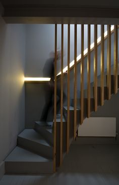 Oak slatted balustrades against dark grey staircase with recessed oak handrail and LED light
