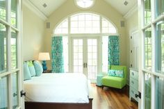 The designer turned to local craftspeople for the custom bed frame and bedside tables. The Charles Stewart chair is swathed in a punchy green fabric. Gourd-shaped Robert Abbey table lamps and ocean-hued draperies add pattern and interest to this girls' room.