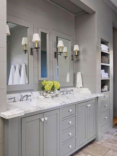An easy-to-live with shade of medium gray takes center stage in this neutral bathroom. Horizontal tongue-and-groove paneling brings texture to the monochromatic scheme. A white marble countertop with gray veining keys off the room's primary color, while adding a visual break in the sea of gray./